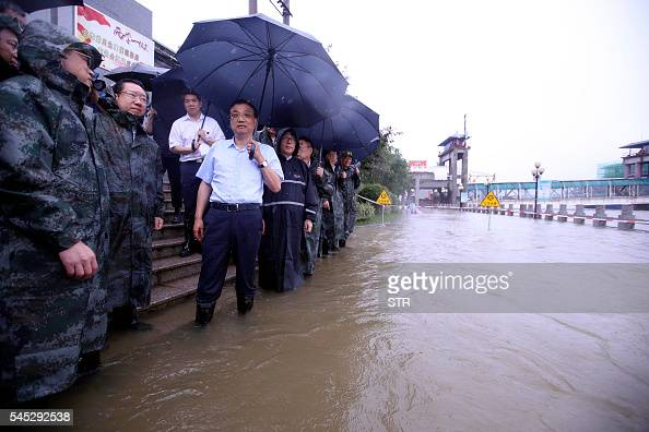 This picture taken on July 6 2016 shows Chinese Premier Li Keqiang visiting Wuhan's Yangtze River embankment to inspect flood control and relief work...