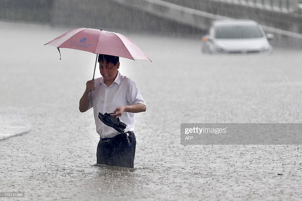 This picture taken on July 7, 2013 shows a man walking on a flooded street holding his hands in Wuhan, central China's Hubei province after a heavy storm. A strong storm hit Wuhan on July 6 and July 7, paralysing transport in multiple places, local media reported. CHINA