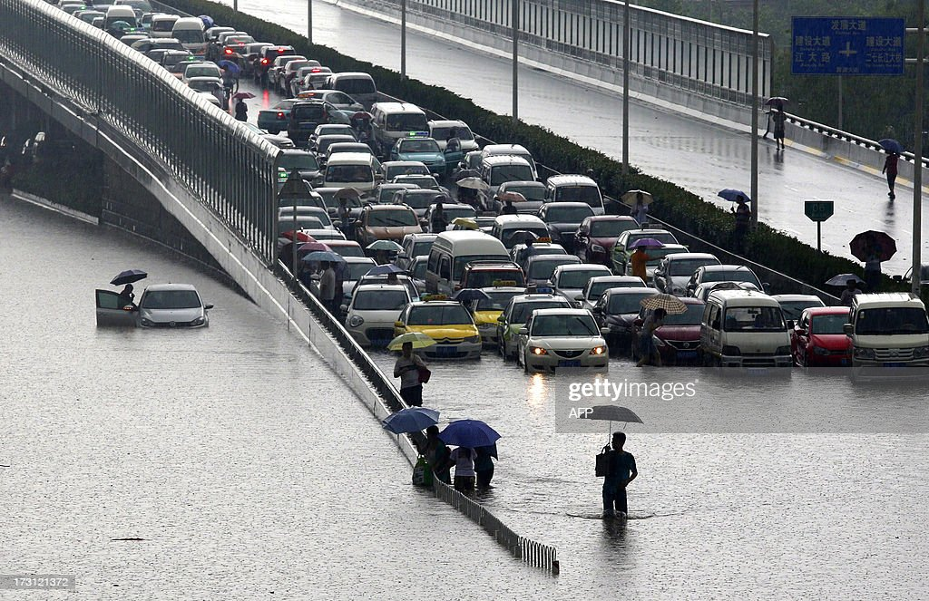 This picture taken on July 7, 2013 shows cars trapped on a flooded street in Wuhan, central China's Hubei province after a heavy storm. A strong storm hit Wuhan on July 6 and July 7, paralysing transport in multiple places, local media reported. CHINA OUT AFP PHOTO