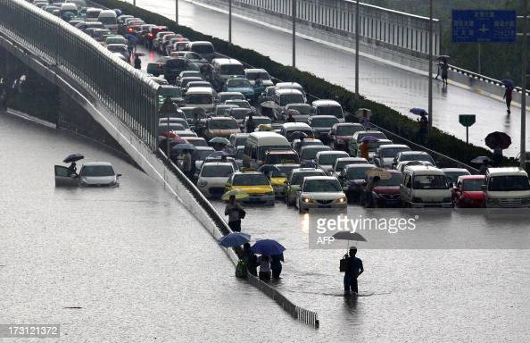 This picture taken on July 7 2013 shows cars trapped on a flooded street in Wuhan central China's Hubei province after a heavy storm A strong storm...