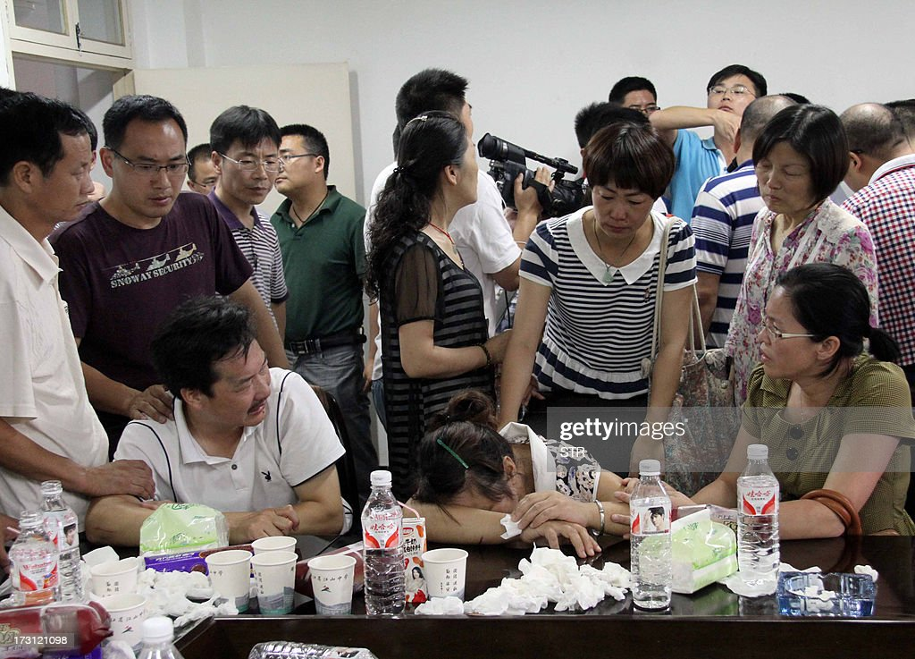 This picture taken on July 7, 2013 shows family members of Wang Linjia, one of the two teenage girls killed after a South Korean passenger jet crashed at San Francisco airport, grieving after they heard the news, in Jiangshan, east China's Zhejiang province. China mourned two teenage girls killed after a South Korean passenger jet crashed at San Francisco airport as survivors recounted harrowing details of their flight, as Chinese nationals made up 141 of the 291 passengers aboard the Asiana Airlines Boeing 777 which burst into flames after it landed short of the runway, injuring 182. CHINA OUT AFP PHOTO