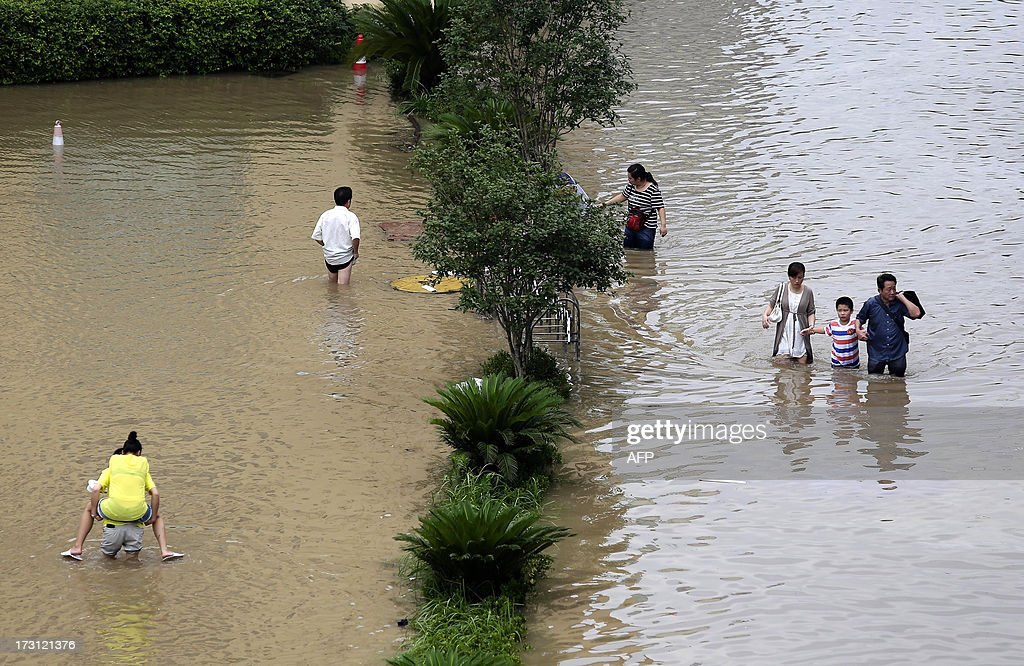 This picture taken on July 7, 2013 shows people walking in a flooded area in Wuhan, central China's Hubei province after a heavy storm. A strong storm hit Wuhan on July 6 and July 7, paralysing transport in multiple places, local media reported. CHINA