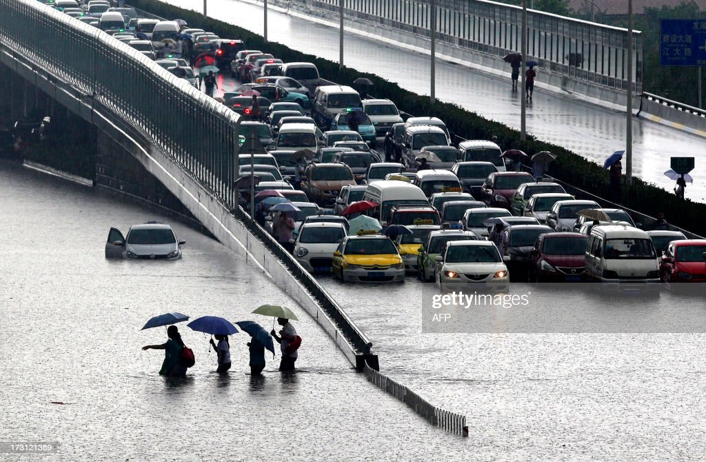 This picture taken on July 7, 2013 shows people walking through a flooded street in Wuhan, central China's Hubei province after a heavy storm. A strong storm hit Wuhan on July 6 and July 7, paralysing transport in multiple places, local media reported. CHINA