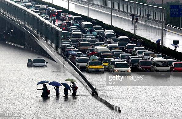This picture taken on July 7 2013 shows people walking through a flooded street in Wuhan central China's Hubei province after a heavy storm A strong...