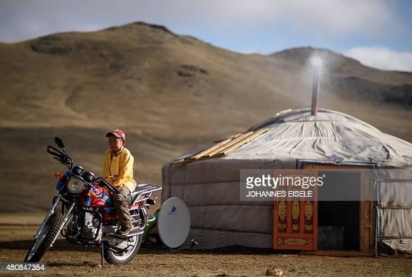 This picture taken on July 8 2015 shows 13yearold jockey Purevsurengiin Togtokhsuren sitting on a motorbike next to his 'yurt' after taking care of...