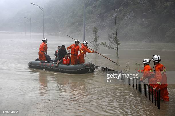 This picture taken on July 9 2013 shows rescuers looking for victims as heavy flood waters sweep through Beichuan in southwest China's Sichuan...