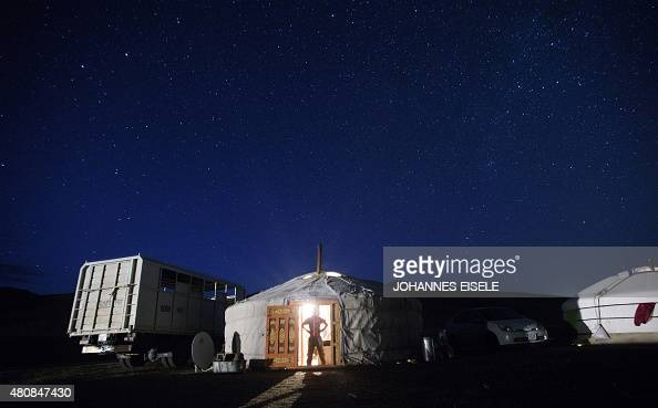 This picture taken on July 9 2015 shows 13yearold jockey Purevsurengiin Togtokhsuren posing at nighttime for a picture at the entrance of his 'yurt'...