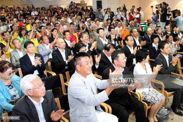 This picture taken on July 9 2017 shows residents in Munakata city celebrating following the news that Okinoshima its nearby reefs and four other...