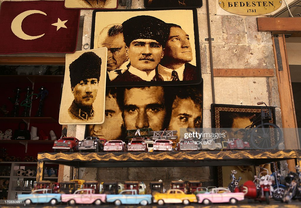 This picture taken on June 11 2013 shows embroidered images of Mustafa Kemal Ataturk the founder of modern Turkey and toy cars in a shop of the...