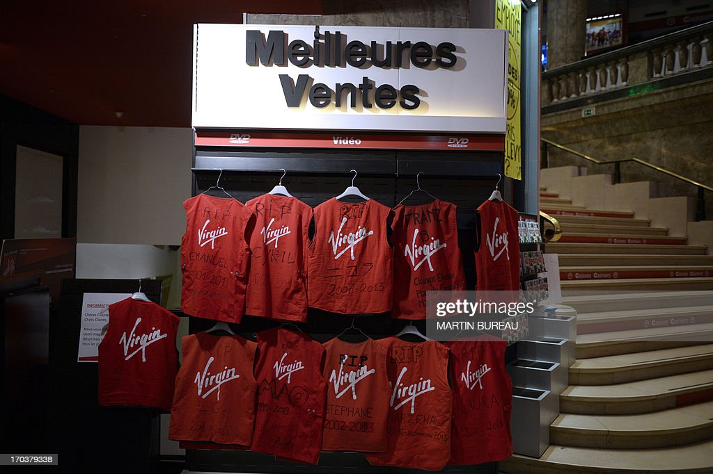 This picture taken on June 12, 2013 as Virgin's employees occupy the Champs-Elysees Virgin Megastore, in Paris, shows the employees' red vests under a giant sign 'Best sales', inside the store. Virgin Megastore's management announced on June 12 that its 26 shops will close on this day for 'security reasons', as some of them were occupied since June 11 by employees asking for better monetary compensations after the shutting down of the company.