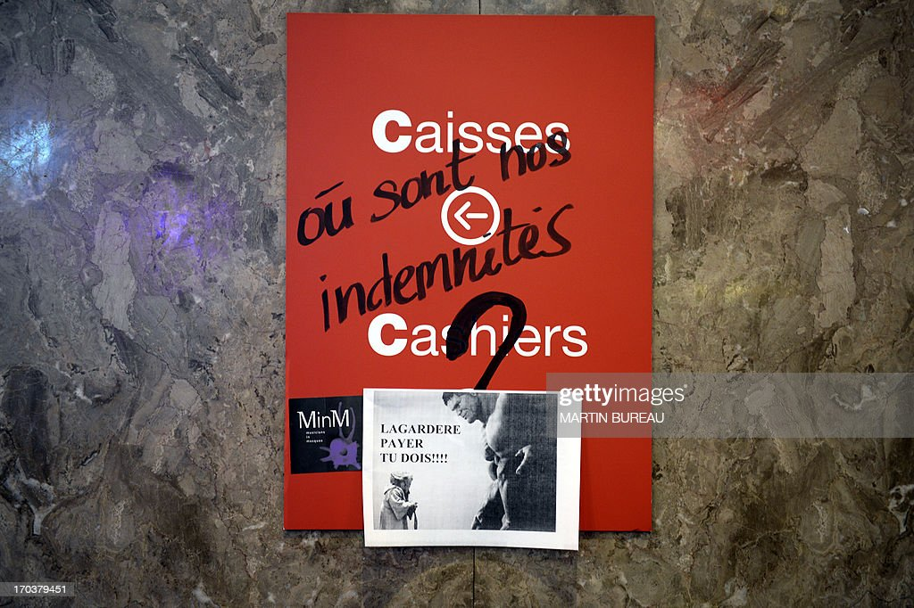 This picture taken on June 12, 2013 as Virgin's employees occupy the Champs-Elysees Virgin Megastore, in Paris, shows a cashiers' sign tagged with an inscription reading 'Where are our compensations?', inside the store. Virgin Megastore's management announced on June 12 that its 26 shops will close on this day for 'security reasons', as some of them were occupied since June 11 by employees asking for better monetary compensations after the shutting down of the company.
