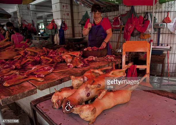 This picture taken on June 17 2015 shows a butcher preparing cuts of dog meat for sale in Yulin in southern China's Guangxi province People from...