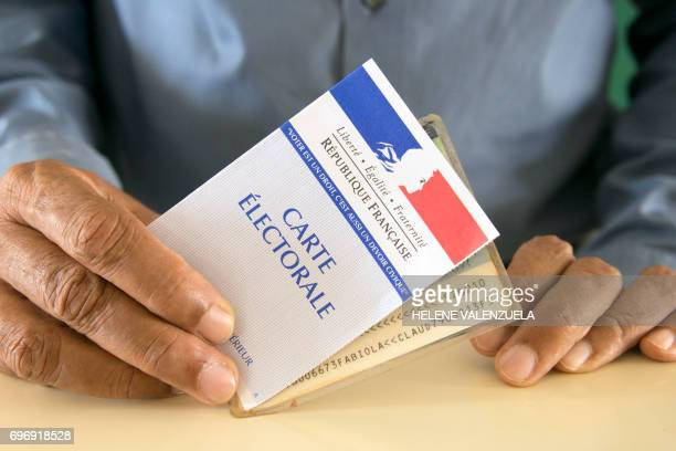 This picture taken on June 17 shows an electoral card and French ID card during the second round of the French legislative elections at a polling...