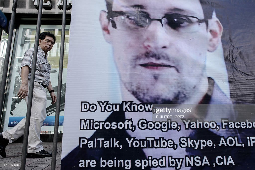 This picture taken on June 18 2013 shows a man walking past a banner displayed in support of former National Security Agency contractor Edward...
