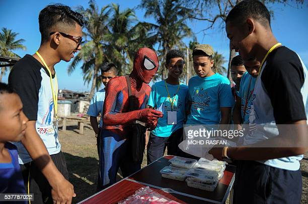 This picture taken on June 2 2016 shows Zawawi Ghazali wearing his SpiderMan suit and selling the popular nasi lemak to customers at Pantai Genting...