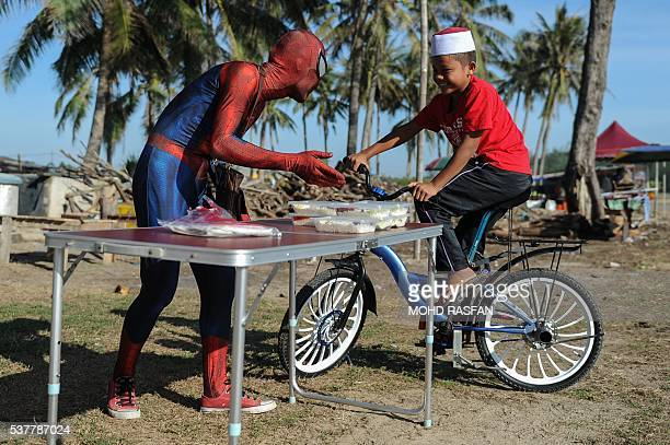 This picture taken on June 2 2016 shows Zawawi Ghazali wearing his SpiderMan suit and selling the popular nasi lemak to a customer at Pantai Genting...