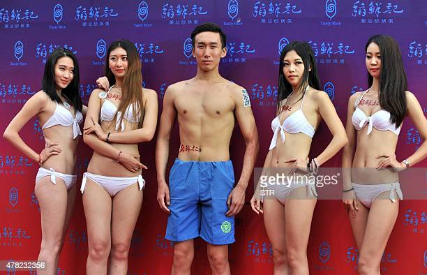 This picture taken on June 20 2015 shows models in bikini and swimming trunks posing outside a newly opened congee restaurant to celebrate the...
