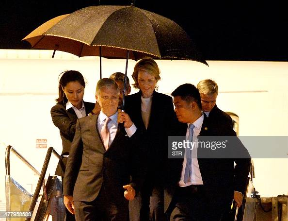 This picture taken on June 20 2015 shows Queen Mathilde and King Philippe of Belgium deplane in the rain as they arrive in Wuhan central China's...