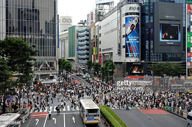 This picture taken on June 21 2008 shows pedestrians crossing the Shibuya intersection in Tokyo Shibuya is one of the city's most colorful and busy...