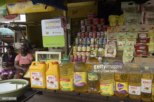 This picture taken on June 21 2016 shows bottles of oil and cans displayed at Magboro market in southwest Nigeria Ogun State Ordinary Nigerians are...