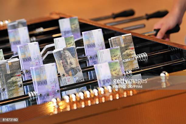 This picture taken on June 23 2008 shows a table football with players substituted by replicas of Swiss Franc notes in Lausanne as part of an...