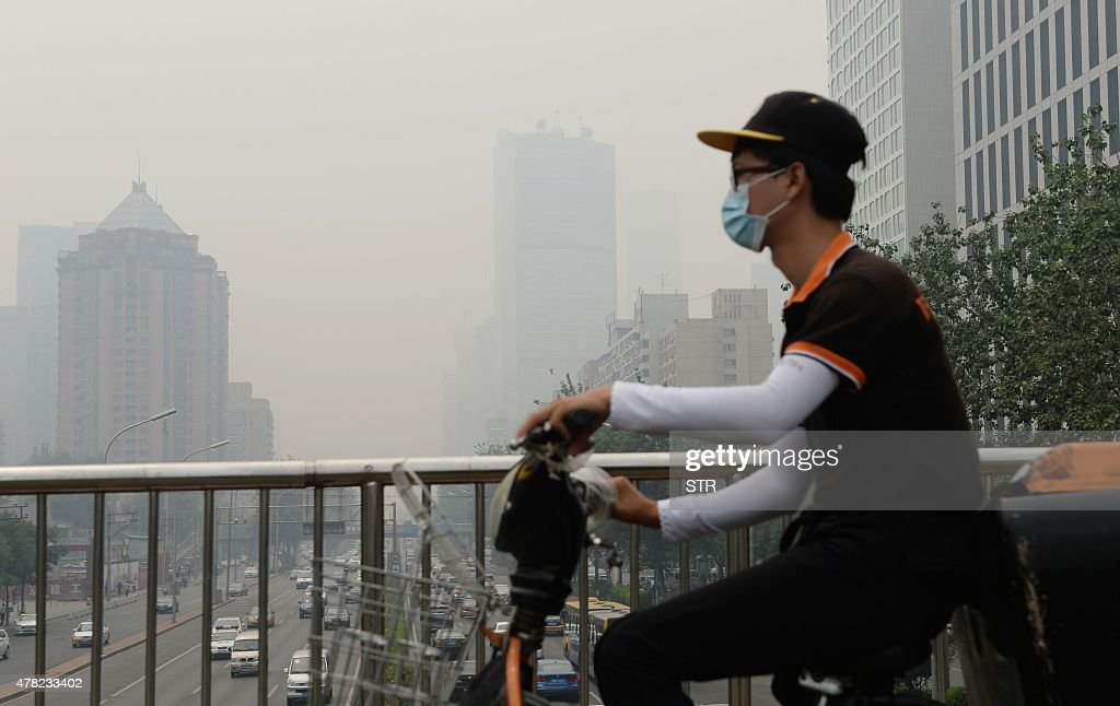 This picture taken on June 23 2015 shows a cyclist wearing a mask in Beijing covered by heavy smog China's cities are often hit by heavy pollution...
