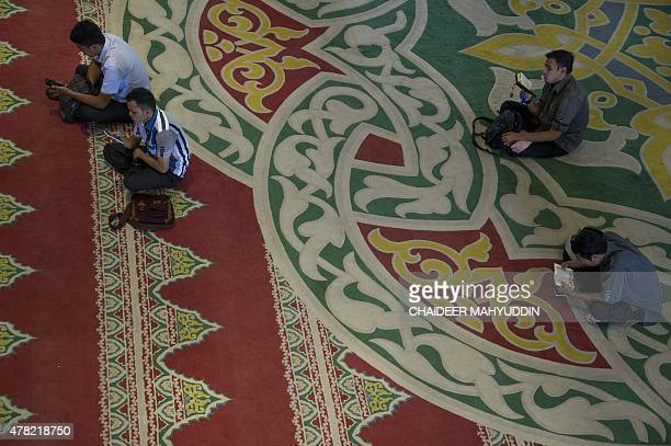 This picture taken on June 23 2015 shows Indonesian men reading copies of the Koran on printed and digital app form during the Muslim holy month of...