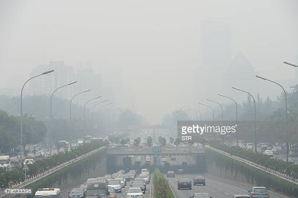 This picture taken on June 23 2015 shows vehicles running in smog covered streets in Beijing China's cities are often hit by heavy pollution blamed...