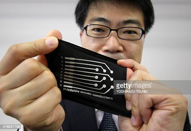 This picture taken on June 24 2015 shows Japan's University of Tokyo professor Takao Someya showing a printed elastic electric conductor on a...