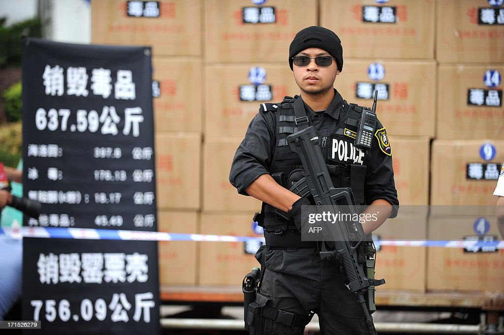 This picture taken on June 25, 2013 shows a policeman standing guard in front of boxes of drugs before they were destroyed in a factory in Guiyang. Guizhou Provincial Narcotics Control Commission destroyed 637.59 kilograms of drugs including heroin and methamphetamine, together with 756.09 kilograms of poppies, to mark the Internatioal Day Against Drug Abuse and Illicit Trafficking on June 26. CHINA OUT AFP PHOTO