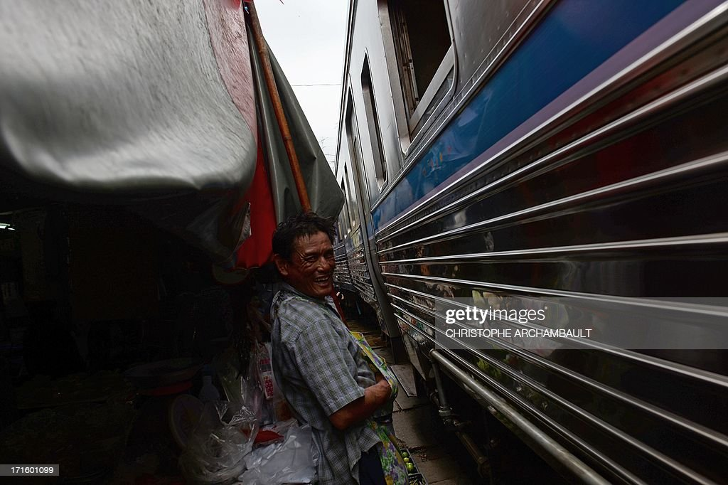 This picture taken on June 25, 2013 shows a shopkeeper standing between his stalls and a passing train at a food market in Maeklong, some 60 kilometers south-west of Bangkok. Several times a day, shopkeepers swiftly pack up their food stalls and pull back their canopies to let the trains pass. Once the trains have rumbled through, the crates of vegetables, fish and eggs, are heaved back into their position along the tracks and shoppers return to the tracks they use as a path through the market. Every day hundreds of tourists armed with cameras flock to the picturesque Maeklong market to witness the well-oiled routine. AFP PHOTO/Christophe ARCHAMBAULT