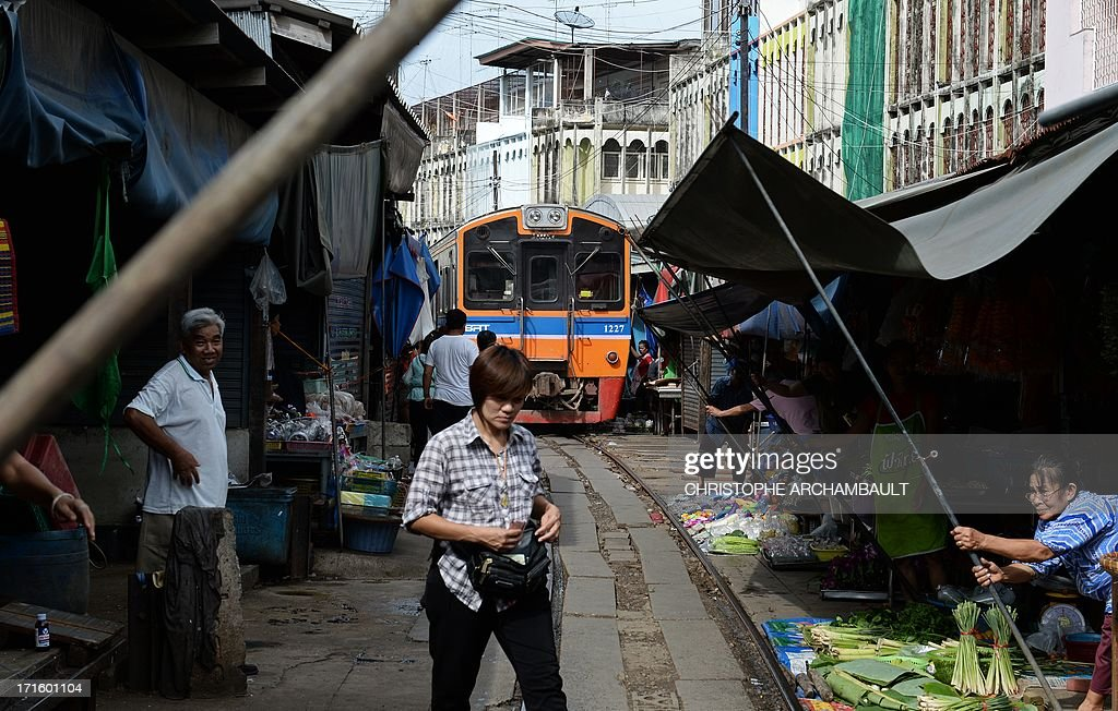 This picture taken on June 25, 2013 shows a train passing through a food market in Maeklong, some 60 kilometers south-west of Bangkok. Several times a day, shopkeepers swiftly pack up their food stalls and pull back their canopies to let the trains pass. Once the trains have rumbled through, the crates of vegetables, fish and eggs, are heaved back into their position along the tracks and shoppers return to the tracks they use as a path through the market. Every day hundreds of tourists armed with cameras flock to the picturesque Maeklong market to witness the well-oiled routine. AFP PHOTO/Christophe ARCHAMBAULT