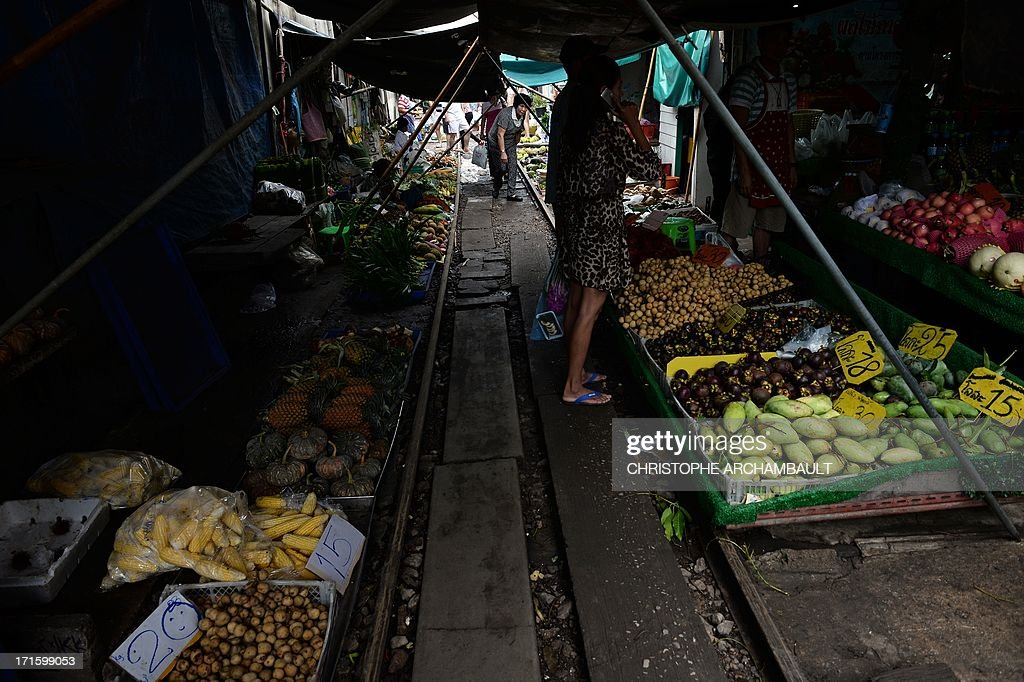 This picture taken on June 25, 2013 shows shoppers walking along a railway track lined up with stalls at a food market in Maeklong, some 60 kilometers south-west of Bangkok. Several times a day, shopkeepers swiftly pack up their food stalls and pull back their canopies to let the trains pass. Once the trains have rumbled through, the crates of vegetables, fish and eggs, are heaved back into their position along the tracks and shoppers return to the tracks they use as a path through the market. Every day hundreds of tourists armed with cameras flock to the picturesque Maeklong market to witness the well-oiled routine. AFP PHOTO/Christophe ARCHAMBAULT