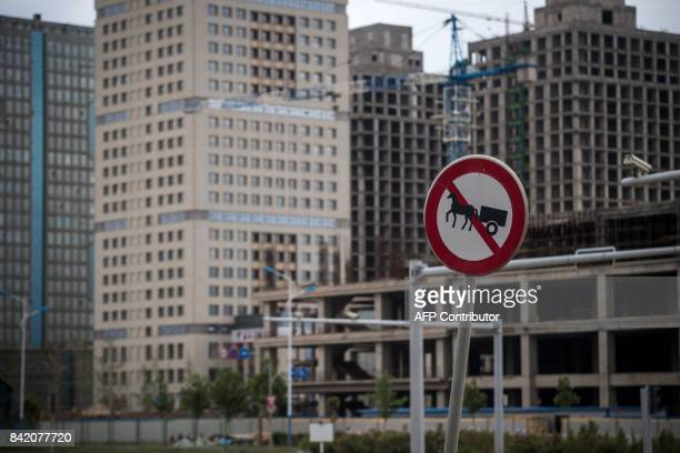 This picture taken on June 25 2017 shows a traffic sign forbidding horse carts to enter in front of a construction site in a development called...