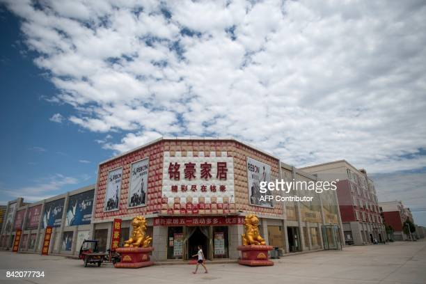 This picture taken on June 25 2017 shows a woman passing a shop in Guangzhou New City a 15 million square metre 'urban centre' on the outskirts of...