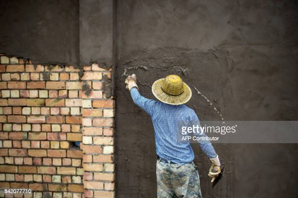 This picture taken on June 25 2017 shows a worker plastering a brick wall in front of a construction site in a development called 'Shenzhen City' on...