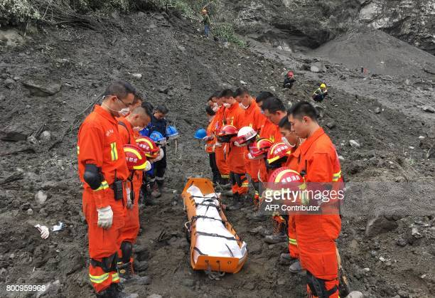 TOPSHOT This picture taken on June 25 2017 shows rescue workers marking a moment of silence next to the body of a victim at the site of a landslide...