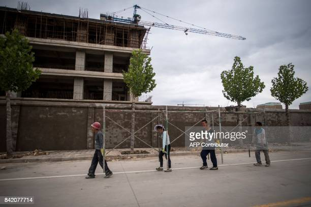 This picture taken on June 25 2017 shows workers carrying scaffolding past a construction site in a development called 'Shenzhen City' on the...