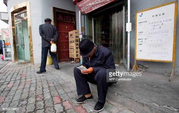 This picture taken on June 27 2017 shows a man looking at his lottery ticket in Tashkurgan China's western Xinjiang province The ChinaPakistan...