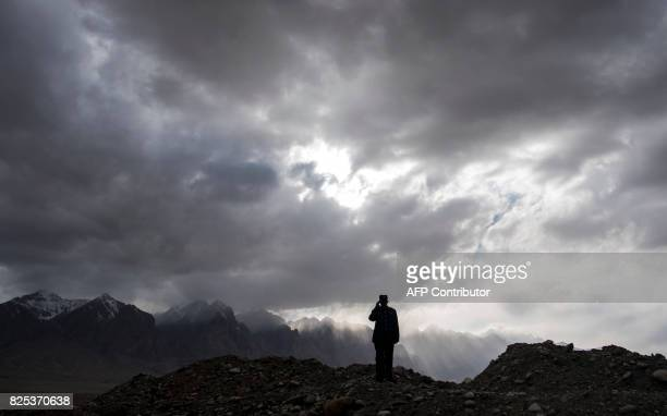 This picture taken on June 27 2017 shows a man using a mobile phone before the Karakorum mountain range next to the ChinaPakistan Friendship Highway...
