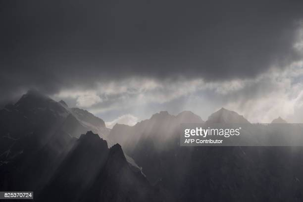 This picture taken on June 27 2017 shows the sun's rays shining through clouds over the Karakorum mountain range next to the ChinaPakistan Friendship...