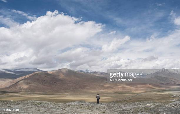 TOPSHOT This picture taken on June 28 2017 shows a man overlooking a section of the ChinaPakistan Friendship Highway and the Karakorum mountain range...