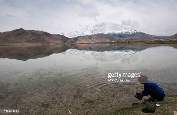TOPSHOT This picture taken on June 28 2017 shows a woman collecting water from the Karakul Lake before the Karakorum mountain range next to the...