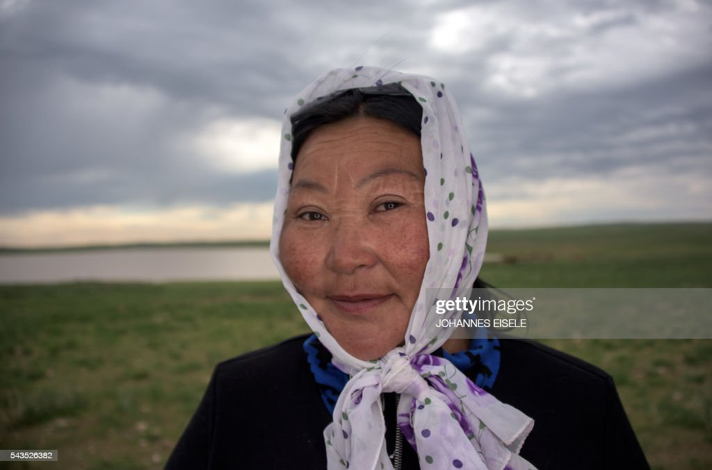 This picture taken on June 29, 2016 shows herder Dambiin Otgontsetseg posing for a picture in the Gobi desert near Luusiin. Mongolians went to the polls across their sprawling, sparsely-populated country on June 29 as it struggles to benefit from its vast natural resources amid disputes over foreign investment and slumping demand from neighbouring China. Across the country -- more than twice the size of France, but with a population of only three million -- trucks with mobile ballot boxes crisscrossed the vast steppe to enable the sick and elderly to vote, while herders and others streamed to polling stations in set up in gers,traditional Mongolian tents. Mongolia-election-politics by Ben Dooley