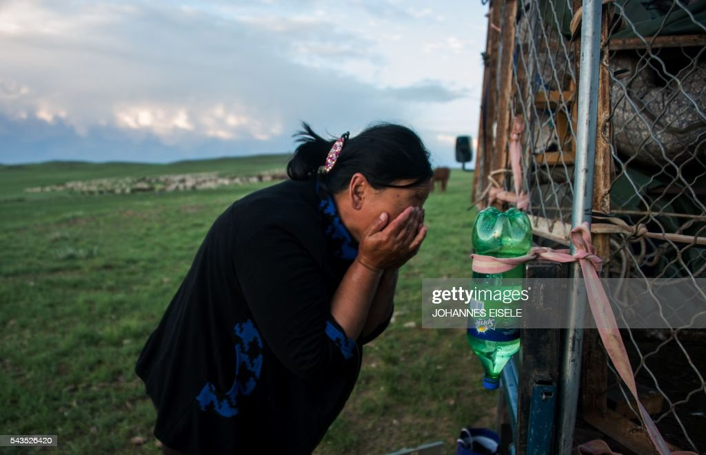 This picture taken on June 29, 2016 shows herder Dambiin Otgontsetseg washing her face from a bottle hanging from the family's mobile home in the Gobi desert near Luusiin. Mongolians went to the polls across their sprawling, sparsely-populated country on June 29 as it struggles to benefit from its vast natural resources amid disputes over foreign investment and slumping demand from neighbouring China. Across the country -- more than twice the size of France, but with a population of only three million -- trucks with mobile ballot boxes crisscrossed the vast steppe to enable the sick and elderly to vote, while herders and others streamed to polling stations in set up in gers,traditional Mongolian tents. Mongolia-election-politics by Ben Dooley