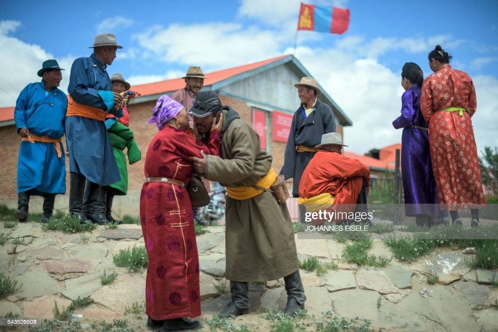 This picture taken on June 29, 2016 shows herder Pagvajaviin Shatarbaatar being greeted by an elderly woman in front of a polling station in Mandalgovi in the Gobi desert. Mongolians went to the polls across their sprawling, sparsely-populated country on June 29 as it struggles to benefit from its vast natural resources amid disputes over foreign investment and slumping demand from neighbouring China. Across the country -- more than twice the size of France, but with a population of only three million -- trucks with mobile ballot boxes crisscrossed the vast steppe to enable the sick and elderly to vote, while herders and others streamed to polling stations in set up in gers,traditional Mongolian tents. Mongolia-election-politics by Ben Dooley