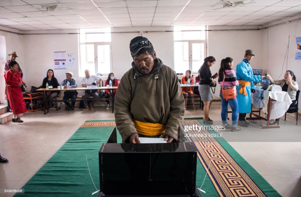 This picture taken on June 29, 2016 shows herder Pagvajaviin Shatarbaatar casting his vote in Mandalgovi in the Gobi desert. Mongolians went to the polls across their sprawling, sparsely-populated country on June 29 as it struggles to benefit from its vast natural resources amid disputes over foreign investment and slumping demand from neighbouring China. Across the country -- more than twice the size of France, but with a population of only three million -- trucks with mobile ballot boxes crisscrossed the vast steppe to enable the sick and elderly to vote, while herders and others streamed to polling stations in set up in gers,traditional Mongolian tents. Mongolia-election-politics by Ben Dooley