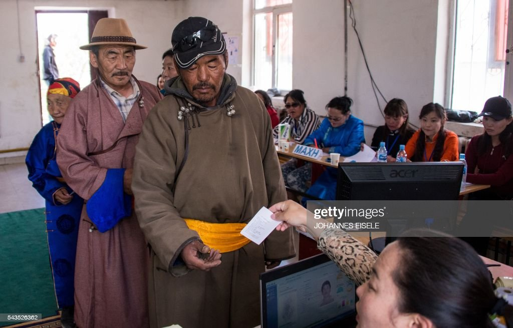 This picture taken on June 29, 2016 shows herder Pagvajaviin Shatarbaatar (C) queuing to cast his vote in Mandalgovi in the Gobi desert. Mongolians went to the polls across their sprawling, sparsely-populated country on June 29 as it struggles to benefit from its vast natural resources amid disputes over foreign investment and slumping demand from neighbouring China. Across the country -- more than twice the size of France, but with a population of only three million -- trucks with mobile ballot boxes crisscrossed the vast steppe to enable the sick and elderly to vote, while herders and others streamed to polling stations in set up in gers,traditional Mongolian tents. Mongolia-election-politics by Ben Dooley
