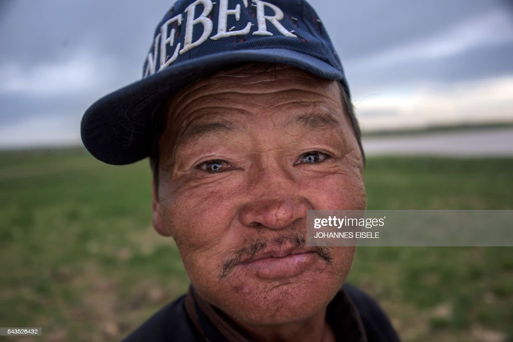 This picture taken on June 29, 2016 shows herder Zandraagiin Budjar posing for a picture in the Gobi desert near Luusiin. Mongolians went to the polls across their sprawling, sparsely-populated country on June 29 as it struggles to benefit from its vast natural resources amid disputes over foreign investment and slumping demand from neighbouring China. Across the country -- more than twice the size of France, but with a population of only three million -- trucks with mobile ballot boxes crisscrossed the vast steppe to enable the sick and elderly to vote, while herders and others streamed to polling stations in set up in gers,traditional Mongolian tents. Mongolia-election-politics by Ben Dooley
