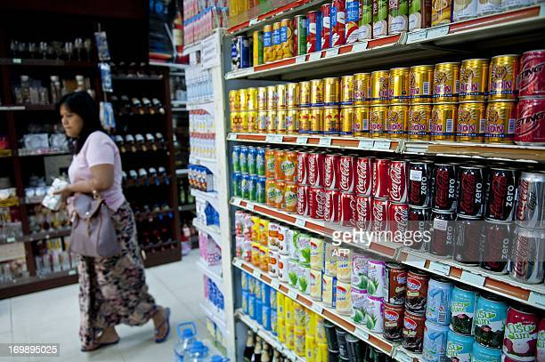 This picture taken on June 3 2013 shows a woman walking past CocaCola cans sitting on a shelf at a supermarket in Yangon CocaCola on June 4 opened a...